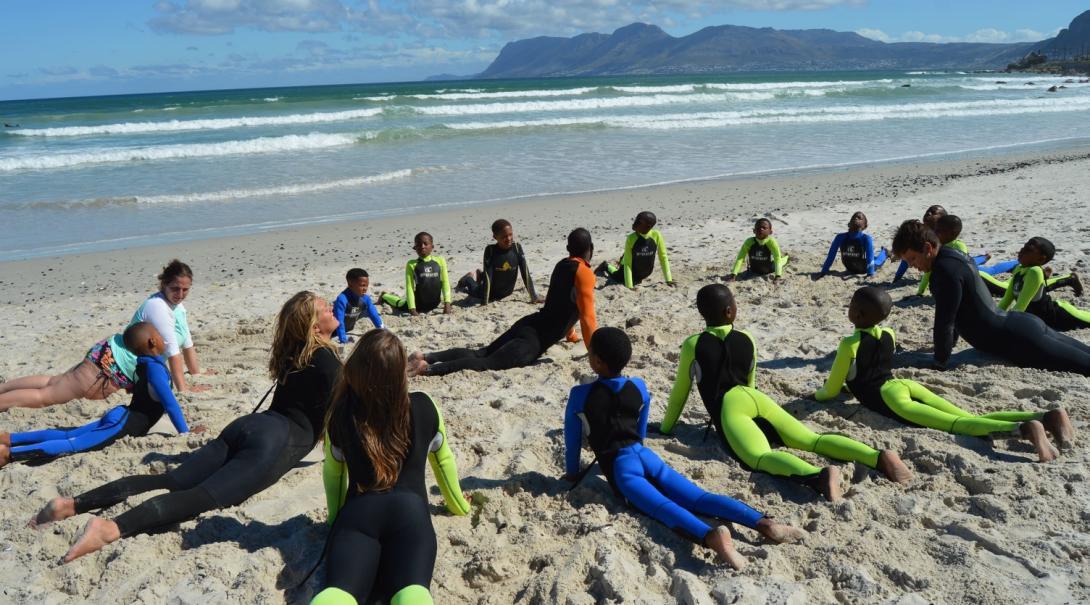 Les volontaires de Projects Abroad s'échauffent et s'étirent avec les enfants sur la plage avant d'aller dans l'eau.